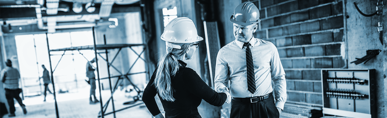 Commercial banner of man and woman, wearing hard hats and shaking hands, with construction being done in the background
