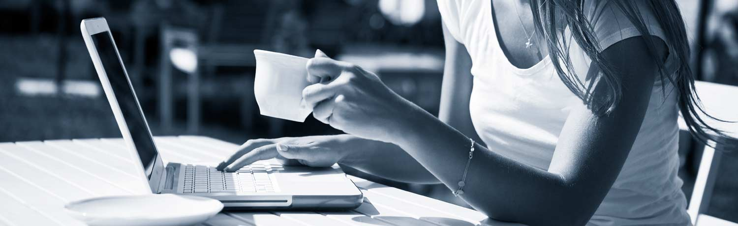 a lady sitting at a table, drinking coffee and using a laptop